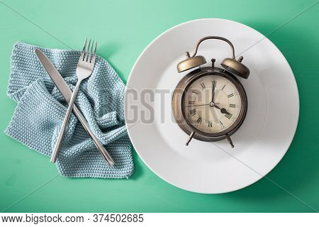 concept of intermittent fasting, ketogenic diet, weight loss. fork and knife crossed and alarmclock on plate