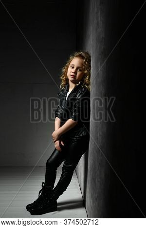 Little Blonde Curly Kid In Black Leather Jacket, Pants And Boots. She Is Standing Leaning On Gray Wa