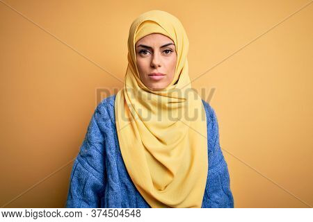 Young beautiful brunette muslim woman wearing arab hijab over isolated yellow background Relaxed with serious expression on face. Simple and natural looking at the camera.