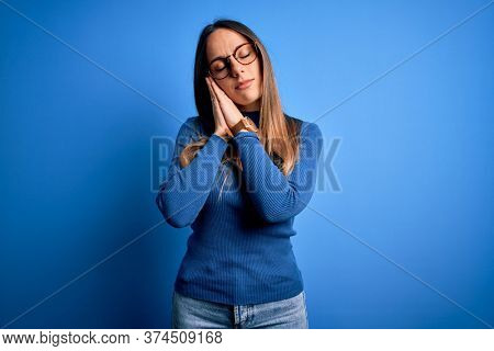 Young beautiful blonde woman with blue eyes wearing glasses standing over blue background sleeping tired dreaming and posing with hands together while smiling with closed eyes.