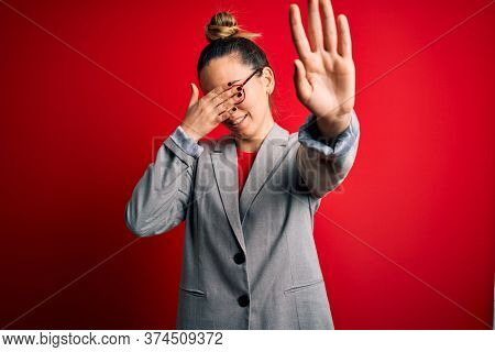 Young beautiful blonde businesswoman with blue eyes wearing glasses and jacket covering eyes with hands and doing stop gesture with sad and fear expression. Embarrassed and negative concept.
