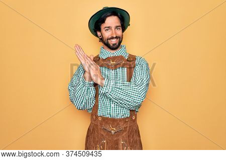 Young handsome man wearing tratidional german octoberfest custome for Germany festival clapping and applauding happy and joyful, smiling proud hands together