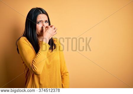 Young brunette woman with blue eyes wearing casual sweater over yellow background smelling something stinky and disgusting, intolerable smell, holding breath with fingers on nose. Bad smell
