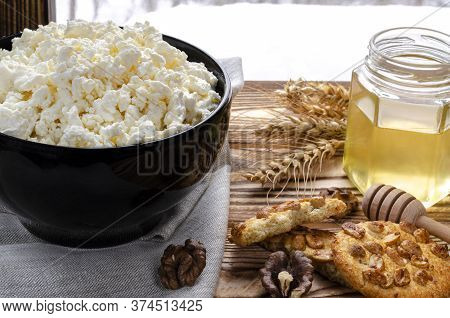 Organic Food. The Textured Curd Lies In A Black Plate Next To Honey, Homemade Pastries And Wheat Ear