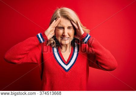 Middle age beautiful blonde woman wearing casual sweater over isolated red background with hand on head for pain in head because stress. Suffering migraine.