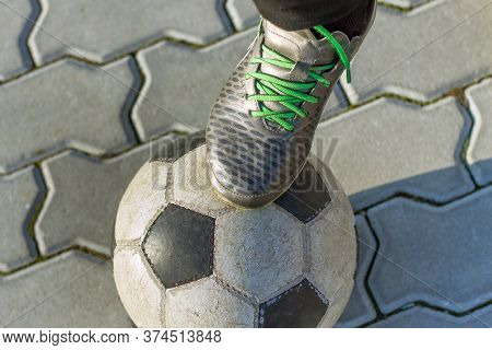 Close-up Of Boy Foot In Sport Shoes On Football Ball Outdoors On Sunny Pavement Background. Vacation