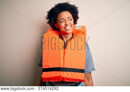 Young African American afro woman with curly hair wearing orange protection lifejacket looking away to side with smile on face, natural expression. Laughing confident.