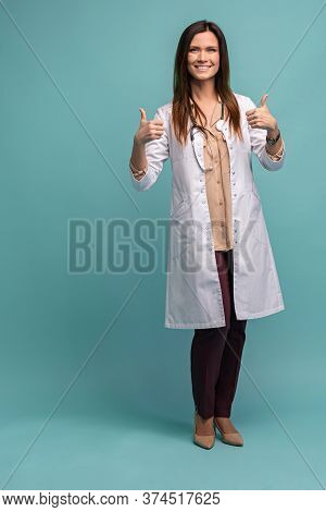 Friendly Female Doctor With Thumbs Up - Isolated Over Light Blue.