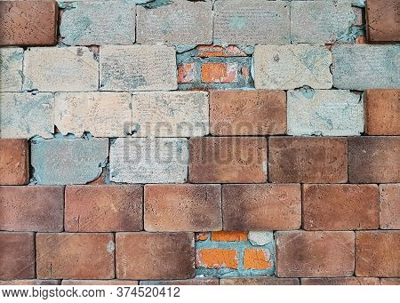Old Brown Brick Wall With Partially Destroyed Facing. Retro Vintage Worn Wall Background. Rough Abst