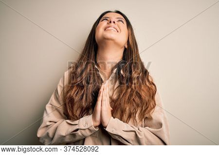 Young beautiful brunette woman wearing casual shirt standing over white background begging and praying with hands together with hope expression on face very emotional and worried. Begging.