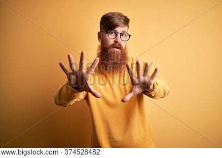 Handsome Irish redhead man with beard wearing glasses over yellow isolated background Moving away hands palms showing refusal and denial with afraid and disgusting expression. Stop and forbidden.