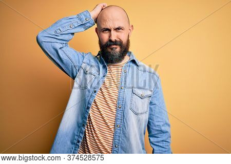 Handsome bald man with beard wearing casual denim jacket and striped t-shirt confuse and wonder about question. Uncertain with doubt, thinking with hand on head. Pensive concept.