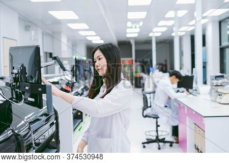 Young Female Scientist Working With Automation Blood Analyzer Report In Medical Laboratory.