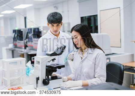 Two Medical Scientist Working In Medical Laboratory , Young Female Scientist Looking At Microscope.