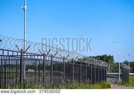 The Restricted Area Is Fenced With A Fence With Barbed Wire. A Fence Around A Restricted Area With C