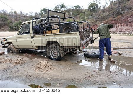 Lifting An Off-road Car With A Jack Made Of Viscous Sandy Soil. Rescue Operations With A Hunting Car