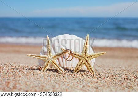 Sea Shells And Starfish With Wedding Rings On The Beach. Summer Vacation Concept. Family Holidays By