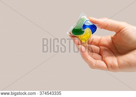 Hand Holds The Dishwasher Capsule On Beige Background. Copy Space. Woman Hand Holding Dishwasher Det