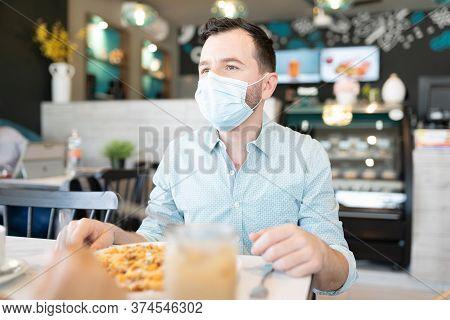 Caucasian Mid Adult Man Having Food In Restaurant During Coronavirus Crisis