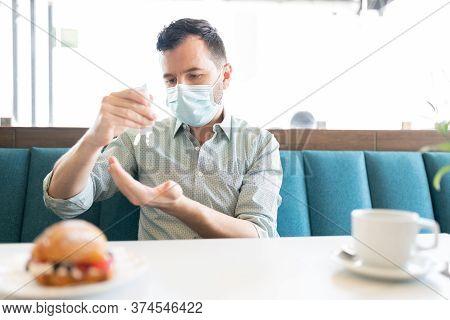 Caucasian Mid Adult Man Applying Sanitizer On Hand In Restaurant During Coronavirus Outbreak