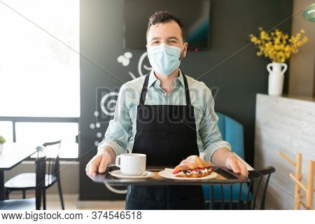 Portrait Of Waiter Wearing Face Mask While Serving Order In Coffee Shop