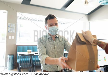 Cropped Hand Of Barista Giving Parcel To Mid Adult Man During Coronavirus Crisis
