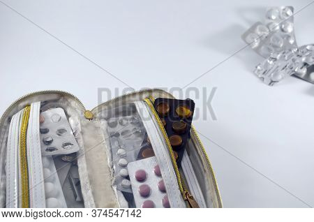 White Handbag, With Half-empty Tablet Blisters On A White Background, Empty Blisters In The Upper Ri