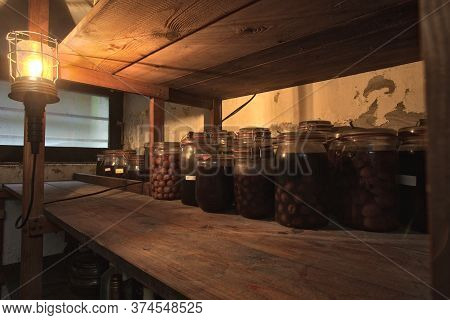 Jars With Pickled Vegetables, Fruity Compotes And Jams In Abandoned Basement With A Light Hanging Pr