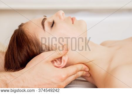 Massage Therapists Hands Are Putting Massage Stones On Eyes Of Young Woman During Eye Massage.