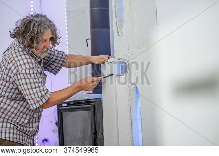 Senior Man Carving In A Wall To Create Beautiful Ornamental Forms Around A Fireplace In A Home.