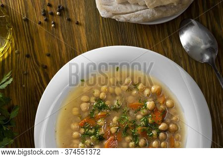 Top View Vegetarian Thick Cheakpea Soup With Corrots And Greens In White Plate On Served Wooden Tabl