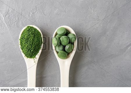 Two White Spoon With Chlorella Or Spirulina On A Grey Concrete Background. Top View.