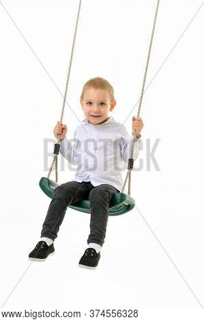 Happy Little Kid Sitting On Rope Swing, Cute Blond Boy Wearing White Shirt And Black Jeans Swinging