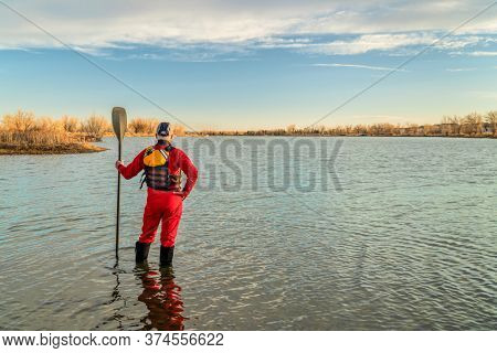 male stand up paddler dressed in a drysuit and life jacket for cold season paddling is contemplating lake view in Colorado, sport and recreation concept