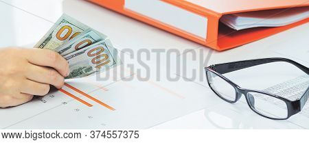 Finance And Business Concept. Small Business Growth. Hand Holding Cash Dollars Stack Over Financial