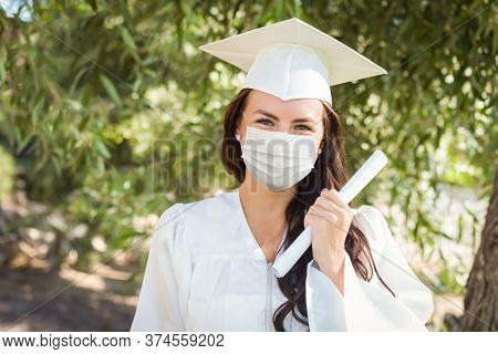 Female Graduate in Cap and Gown Wearing Medical Face Mask.