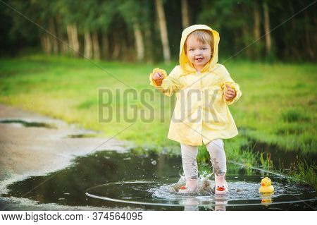 A Baby Girl In A Yellow Jacket Plays With A Rubber Duckling In A Puddle. Soft Focus
