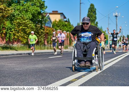 Voronezh, Russia - 24.08.2019 - Disabled Man In Wheelchair Riding Between Runners. Invalid On City R