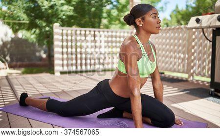 young african american woman doing yoga on backyard deck