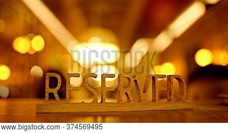 The Inscription Of The Sign Is Reserved Of Wood On A Wooden Table With A Card Side In The Background