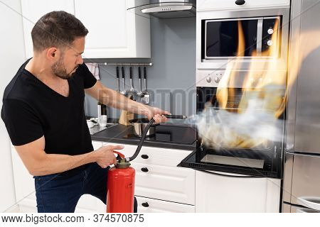 Man Using Fire Extinguisher To Put Out Fire From Oven At Home