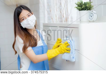 Young Asian Woman In Face Mask And Gloves Cleaning Home In Room, Housekeeper Is Wipe With Fabric, Ho