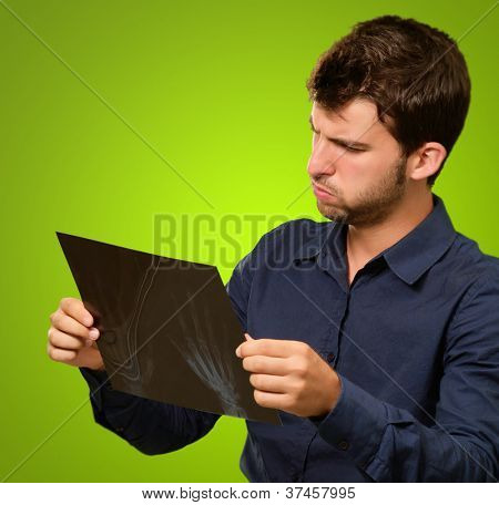 Young Man Looking At X Ray On Green Background