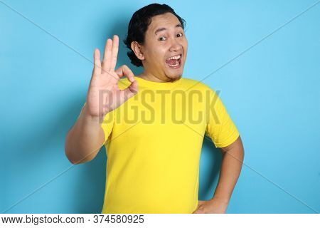Young Asian Man Shows Okay Ok Sign. Close Up Body Portrait Against White Wall