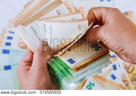 Womans Hands Are Counting Euro Banknotes On A Background Of Euro Banknotes. Spend Money.