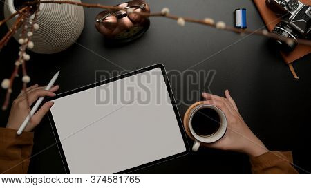 Female Working With Blank Screen Tablet While Right Hand Holding Coffee Cup On Dark Luxury Office De