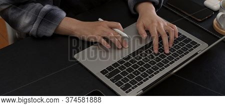 Hands Typing On Laptop Keyboard On Modern Office Desk With Smartphone And Coffee Cup