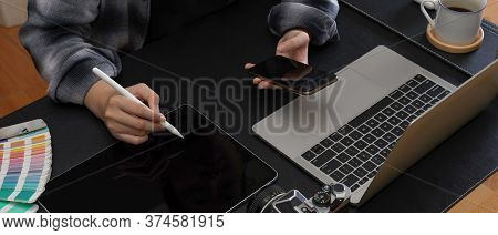 Female Worker Taking Note On Digital Tablet While Looking Information On Smartphone