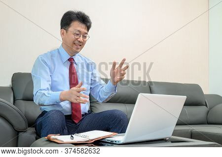 Middle-aged Asian Businessman Sitting On Sofa In Living Room Working At Home. Telecommuting Concept.