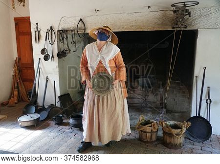 Williamsburg, Virginia, U.s.a - June 30, 2020 - A Lady Inside A Kitchen Wearing A Mask As Required D